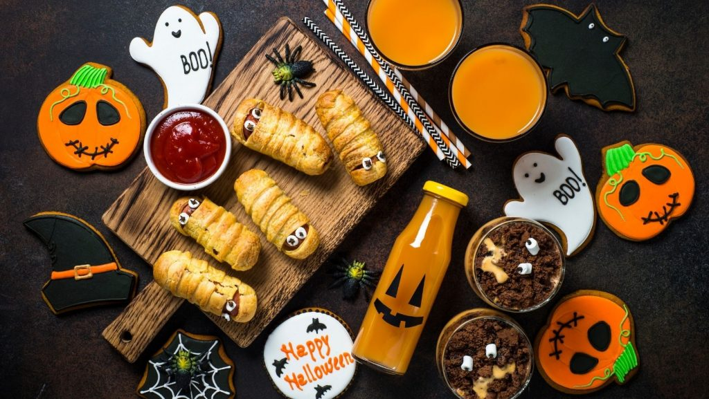 Flat lay of various Halloween treats including cookies, juice, and mummy hot dogs