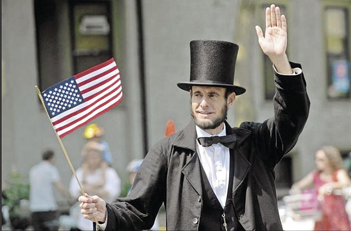 photo of Kevin Wood portraying Lincoln carrying a flag and waving