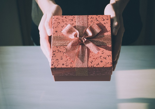 Pair of hands offering a wrapped present