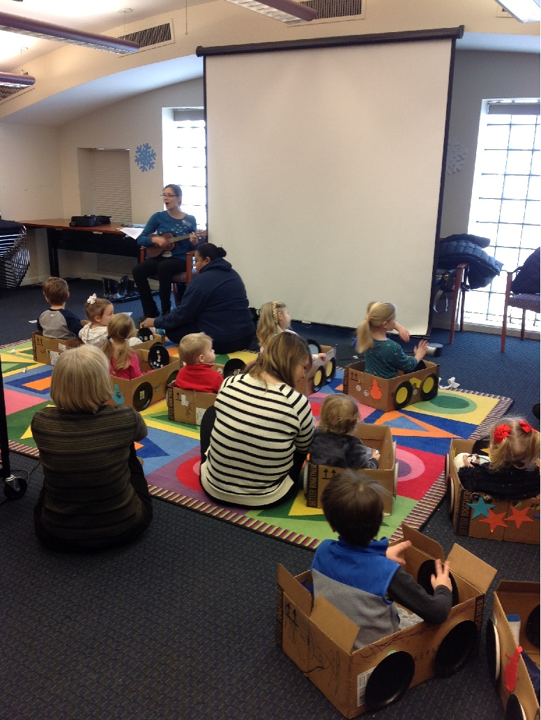 A librarian sings to a group of toddlers in cardboard boxes and their grownups
