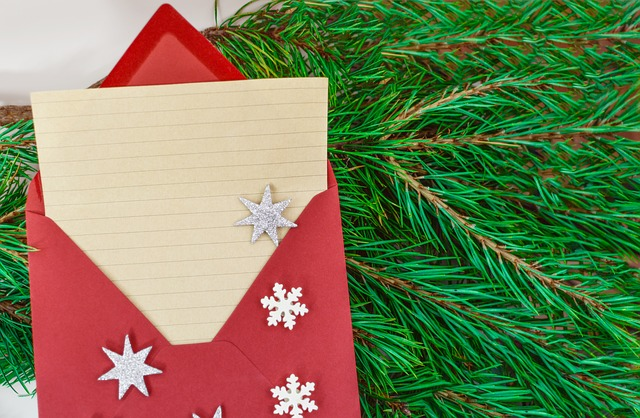 A holiday card in a red envelope, resting on a pine branch