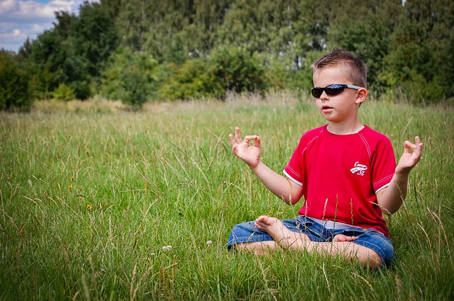Child wearing sunglasses and meditating in a field
