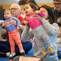 caregivers hold babies during storytime