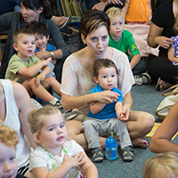 Parents and caretakers participating in family storytime with their children