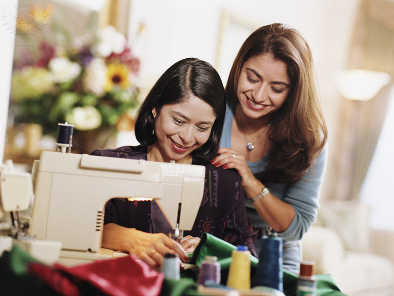 Mother and daughter at sewing machine