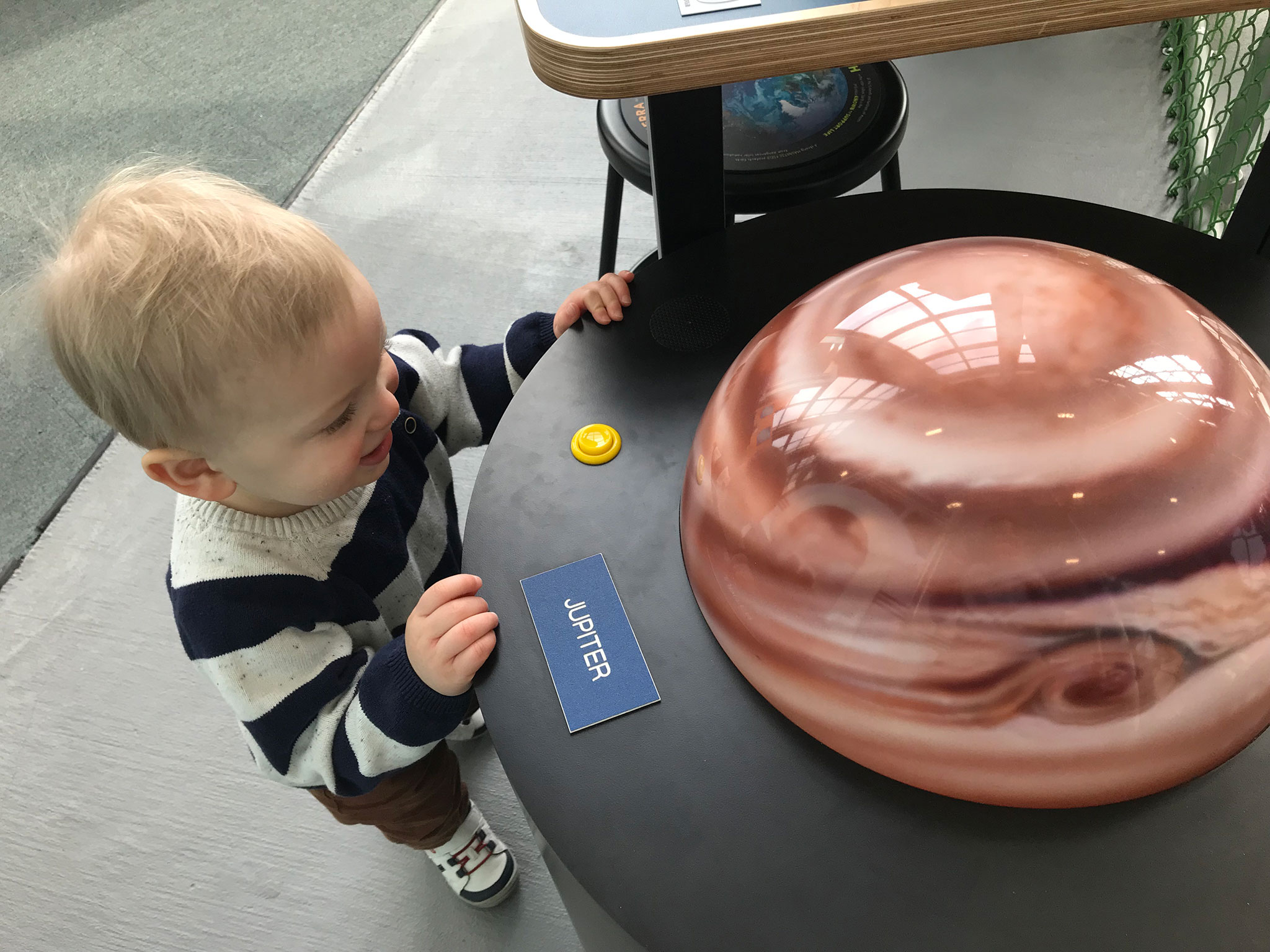 My son looking at a model of Jupiter