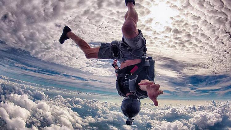 Guy skydiving upside down in clouds