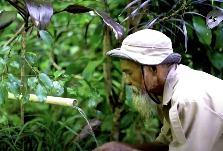 sadiman washing his face with the banyan forest's clean water
