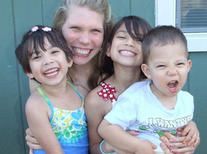 mom hugging her three kids