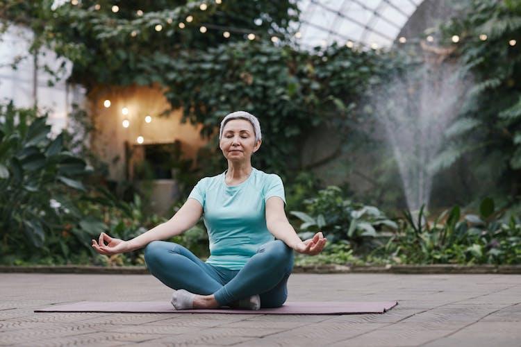 woman meditating on yoga mat