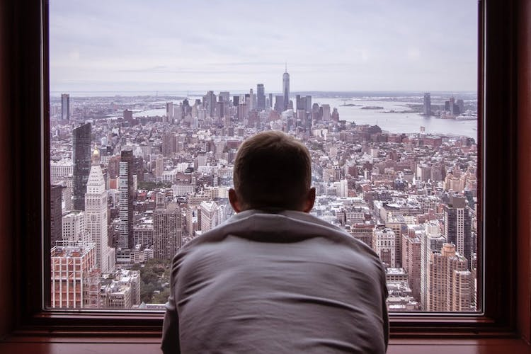 man looking out at city