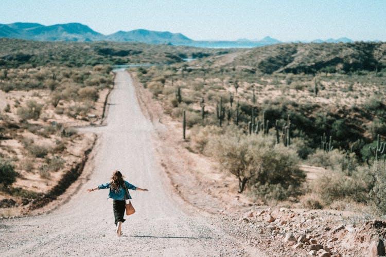 woman walking down a dirt road