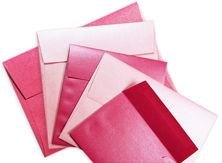 Array of metallic pink invitation envelopes