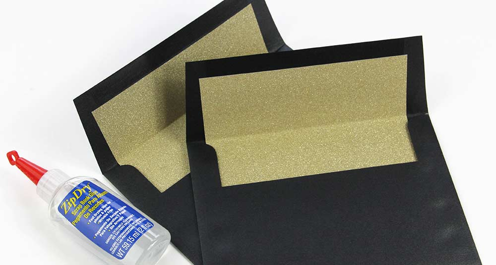 Black metallic envelopes hand lined with gold glitter paper. Materials and step by step instructions from LCI Paper