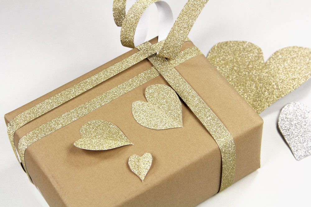 Kraft paper wrapped present with MirriSPARKLE glitter paper heart and band embellishments