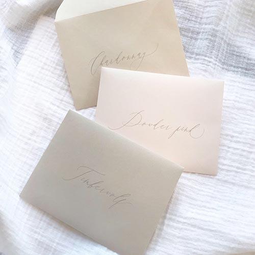 Light gray printing on light gray, blush and taupe envelopes