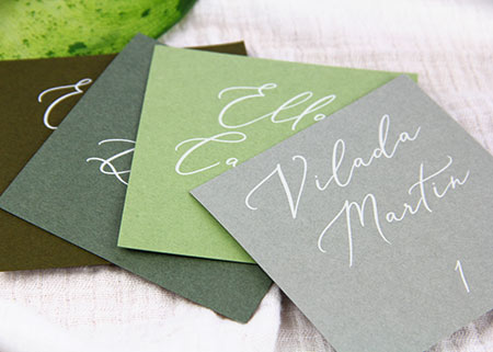 Square flat green place cards printed in white calligraphy font by LCI Paper.