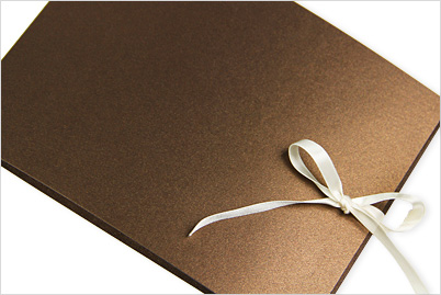 Metallic booklet invitation held closed with decorative satin ribbon