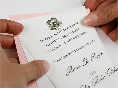 slim three layer vellum invitation secured with floral metal brad