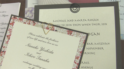 Two invitations embellished with spiral clips