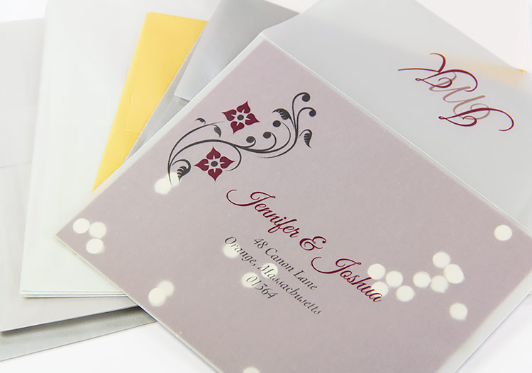 Clear vellum reply envelope printed with floral design and filled with confetti