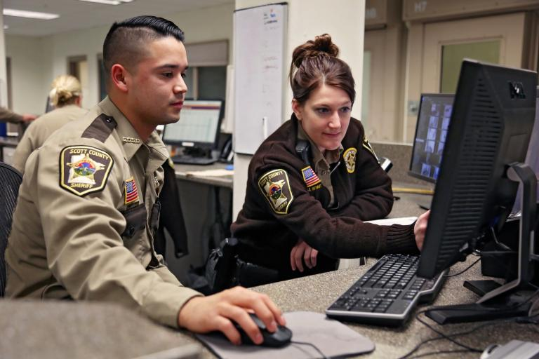 two officers booking a person into a jail on a computer