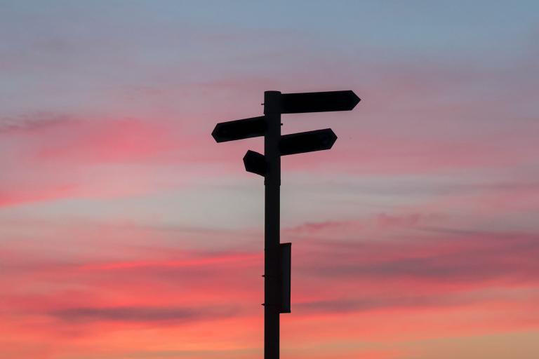 a sign post silhouetted against a sunset