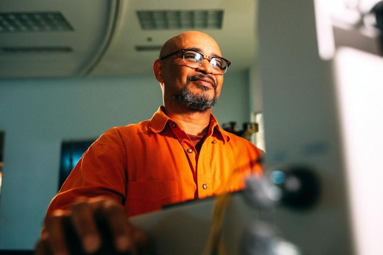 a man in an orange shirt at a computer