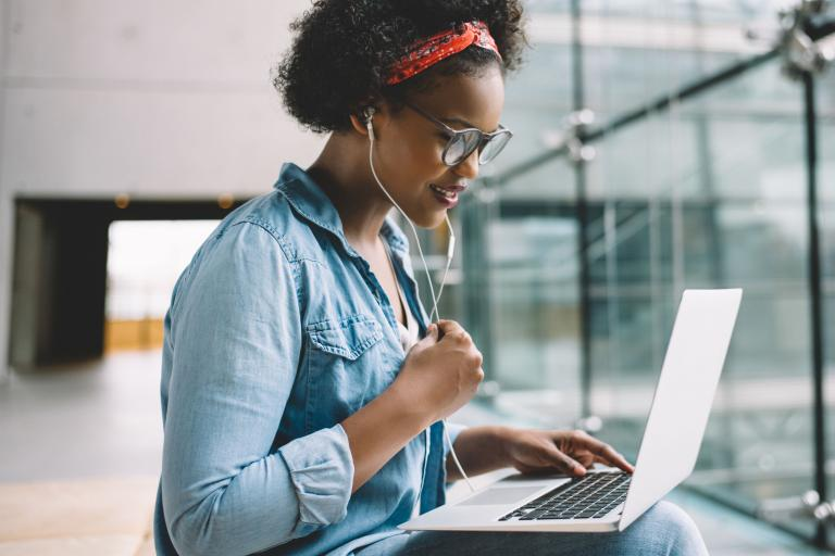 A black woman on a laptop learning cool N.I.C. stuff