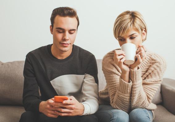 mujer mirando celosa el celular de su pareja