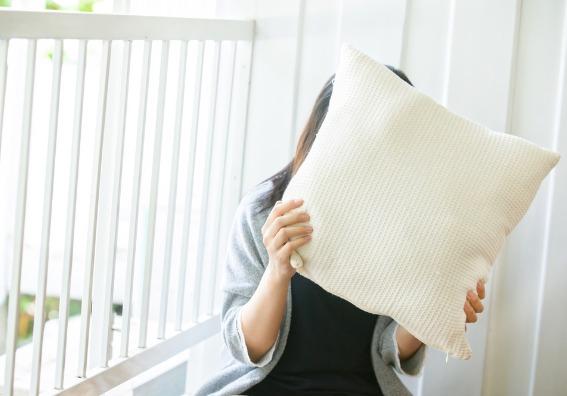 Mujer tapándose con un almohadón