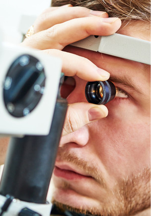 man's eyes checked by an optometrist