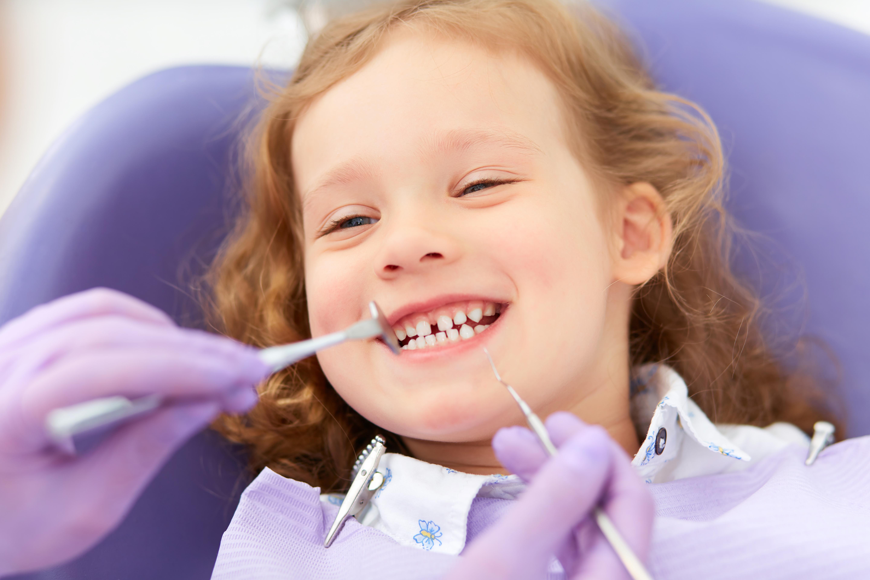 little girl in dentist chair smiling