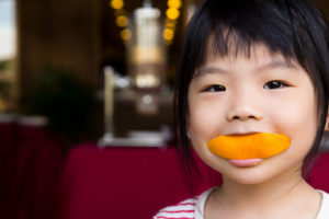 Girl biting orange