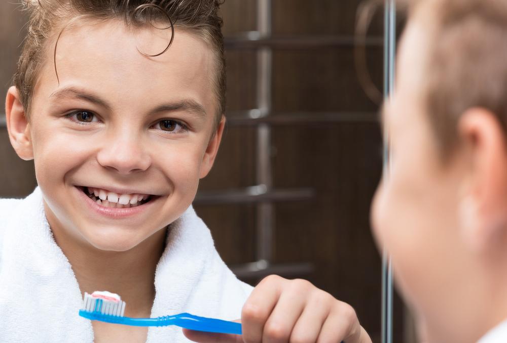 boy in the bathroom brushing his teeth