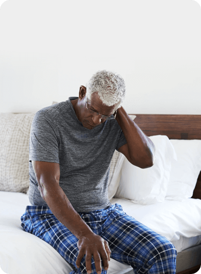 A man sitting on a bed holding his neck in pain