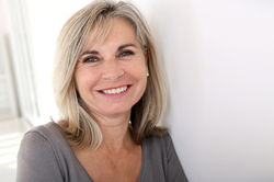 Smiling middle-aged woman in gray shirt