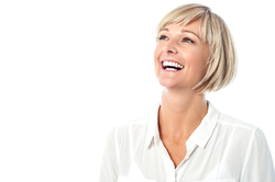 A woman laughing in a white room