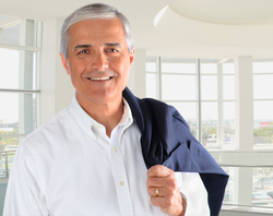 Middle-aged man in business attire smiles at camera