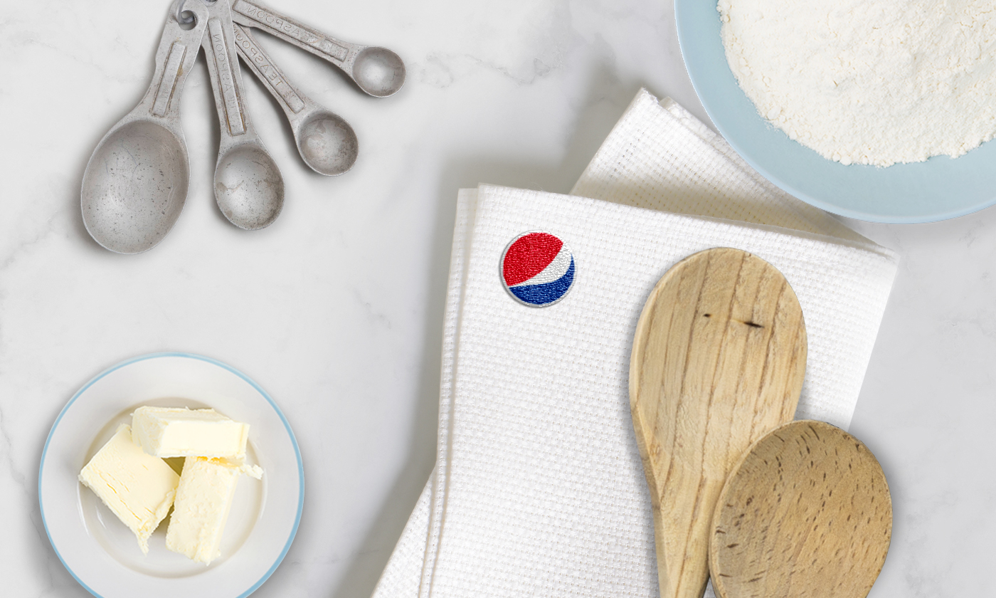 Wooden spoons with butter dish, measuring spoons, flour and a towel with a Pepsi logo