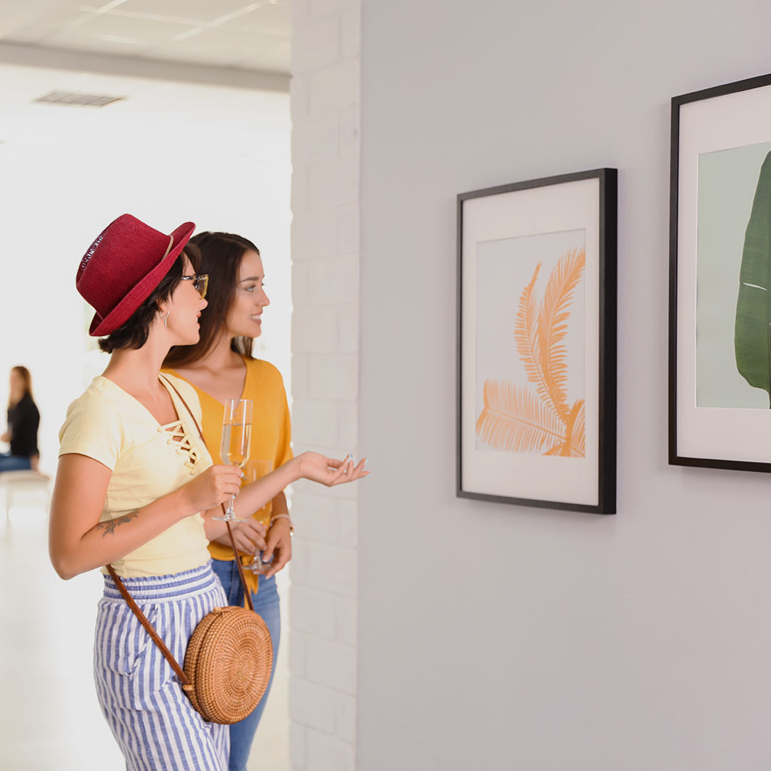 Two women looking at framed art on a wall