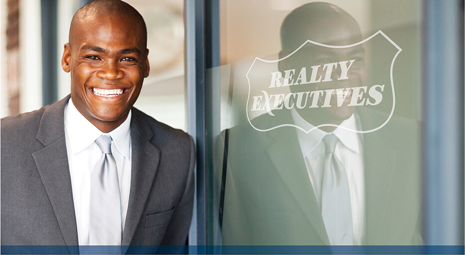 real estate broker standing at a Realty Executives office