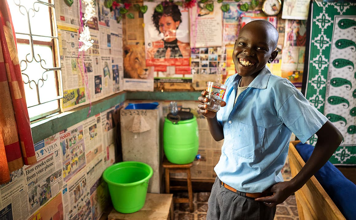 Philip's son enjoys drinking clean water from a household filter provided by Samaritan's Purse.