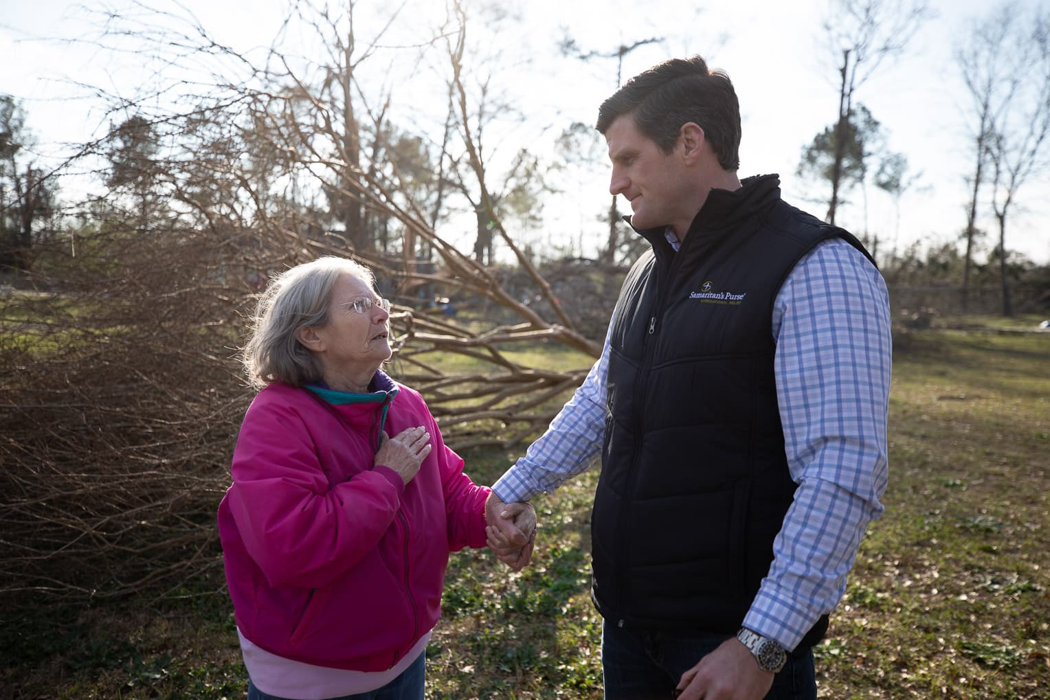 Edward Graham comforts a homeowner after an EF4 tornado and dozens of other twisters ripped through parts of east central Alabama.