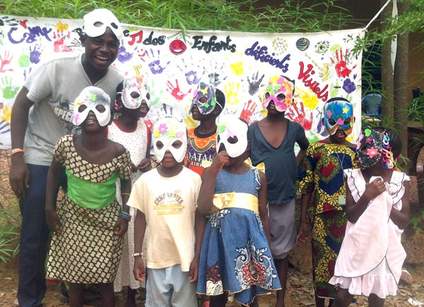 Désiré with children and the masks the made