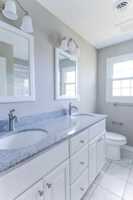 Medford Lakes, NJ - Bertch Quebec style double vanity with Moen Brantford : single handle faucets, framed mirrors, and triple globe lights, in polished chrome.  Meteorite granite top.  Kohler highline comfort height elongated commode.