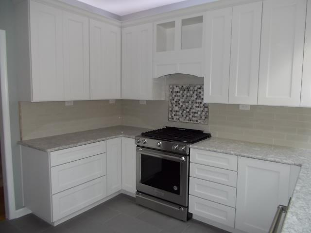 """Medford, NJ - In our Medford kitchen, Cambria countertops in """"Berwyn"""", back-splash field of 3x9 ocean surf gray tiles, and hexagonal river bed marble and glass decorative area over the range."""