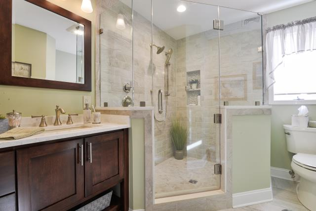 Haddonfield, NJ - Custom niche with grab bars and sliding shower head.  This also has a custom shower glass door.  Variation of different tile through out with different accent pieces!