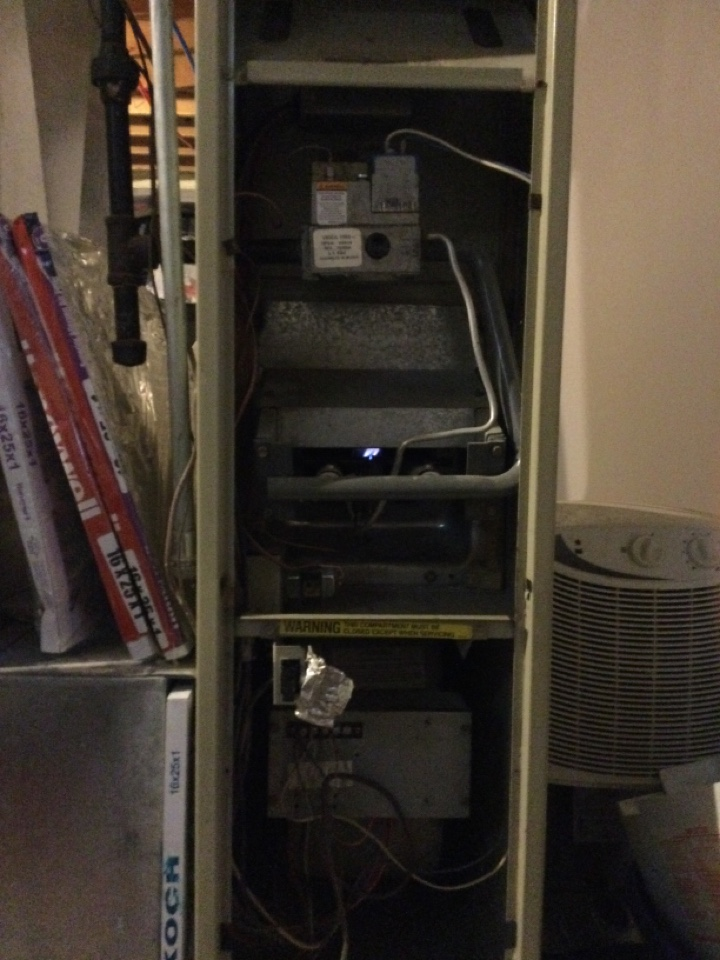 Performing maintenance on a 1987 Snyder general natural draft standing pilot gas furnace.