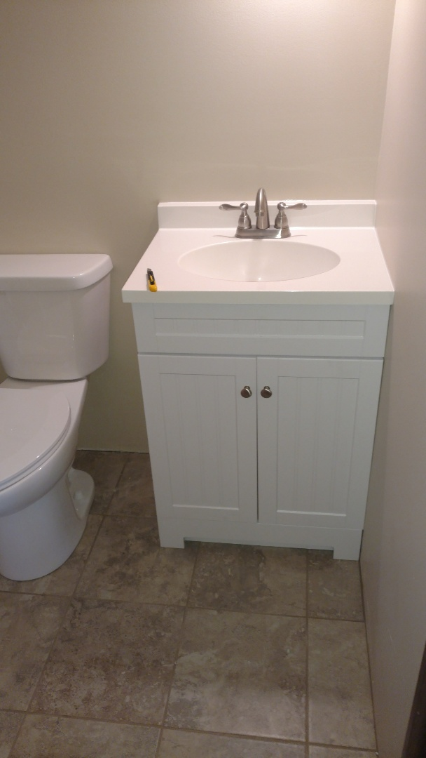 Completed bathroom finish work. Vanity, faucet, toilet and shower trim.